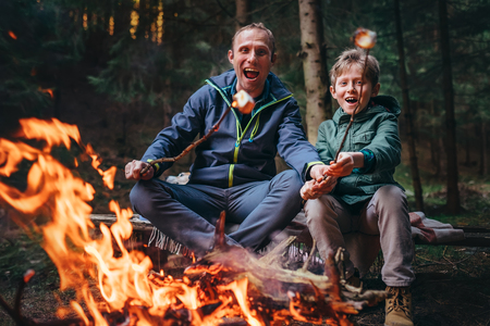 Father and son overroast their marshmallow candies on the campfire