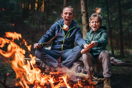 아버지와 아들은 모닥불에 그들의 마시맬로 사탕을 과시했습니다.