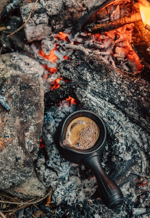 Fresh turkish coffe making in clay cezve on the campfire coals Stock Photo