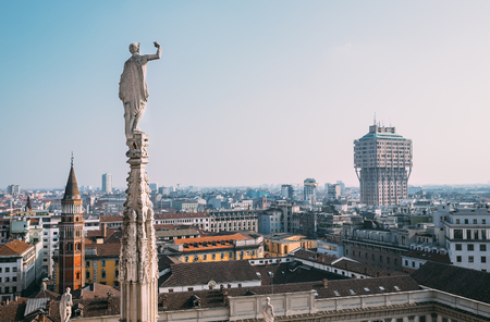 One of numerous ststues Duomo di Milano looks on modern city