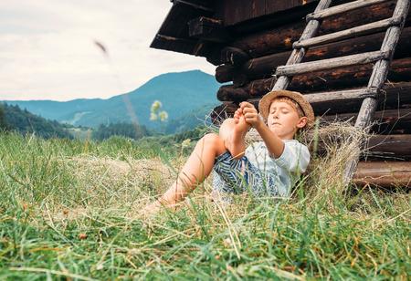 Boy rest in green grass under hayloft in summer afternoon