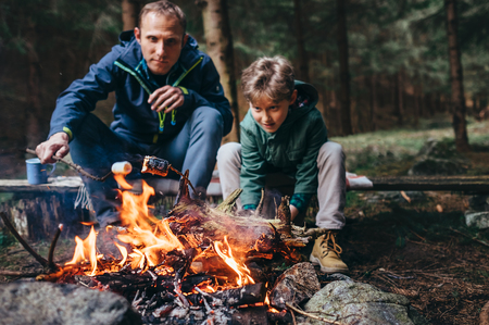 Father and son roast the mashmallow candies on the camp fire