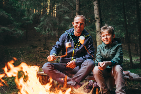 Father and son roast marshmallow candies on the campfire in forest. Spring or autumn camping Archivio Fotografico