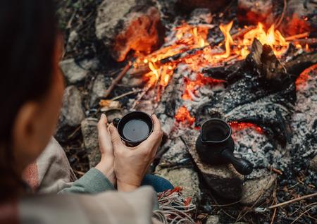 Woman drink a coffee near campfire