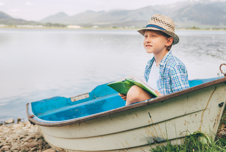 quite: Dreaming boy with book sits in old boat on the mountain lake bank Stock Photo