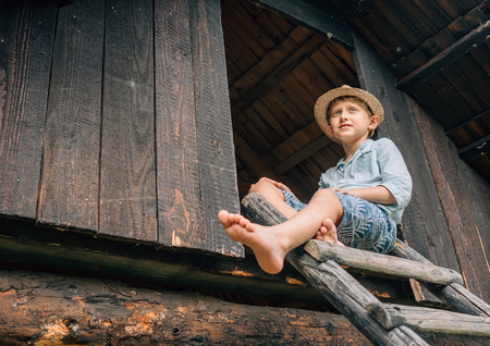 Summer holiday in countrysiade - boy sits on the wood leader to barn