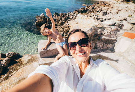 Mother with son take vacation selfie photo in Adriatic Sea Bay Фото со стока