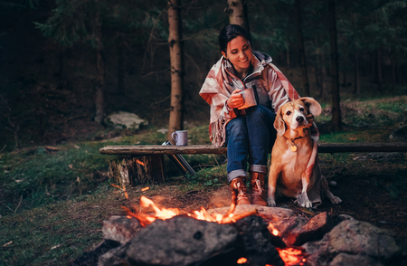 숲에서 여자와 개 가까운 따뜻한 캠프 파이어