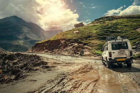 Off-road vehicle goes on the mountain way during the rainy season Stockfoto
