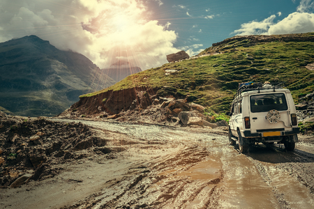 Off-road vehicle goes on the mountain way during the rainy season Foto de archivo