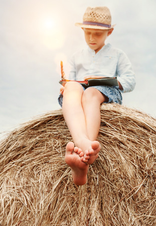 Barefoot boy reads a book sits on the top of haystack Stock Photo