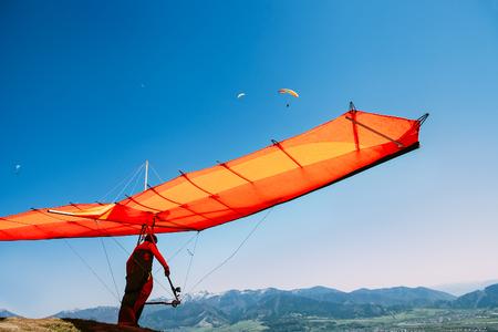 Man met deltavlieger begint te vliegen op de top van de heuvel