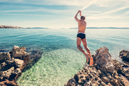 Man jumps in clear crystal water on Adriatic Sea Bay