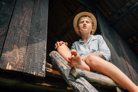 Boy in straw hat sits on the wood leader to barn