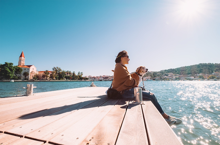 endear: Woman sits with dog on wooden sea pier at sunny windy day Stock Photo