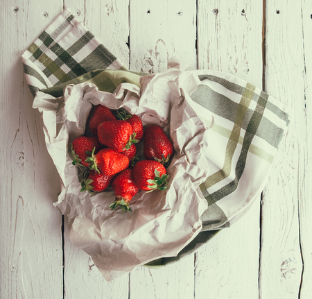 Handful of fresh strawberries is on white wooden table