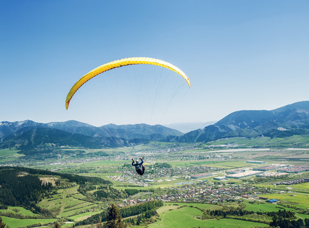 Air sportsman fly on paraplane over the mountain valley