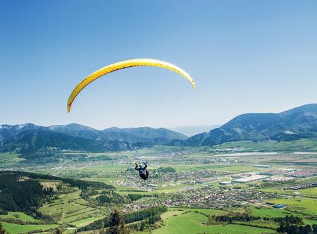 Luchtsportman vliegt op paraplane over de bergvallei Stockfoto
