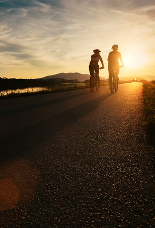 Two cyclists are on sunset road Foto de archivo