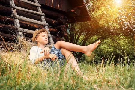 Kleine luie jongen slaapt onder oude hayloft in de tuin