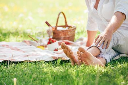 Barfuß Mann sitzt auf einer Decke mit Essen für romantisches Picknick serviert Standard-Bild - 78608722