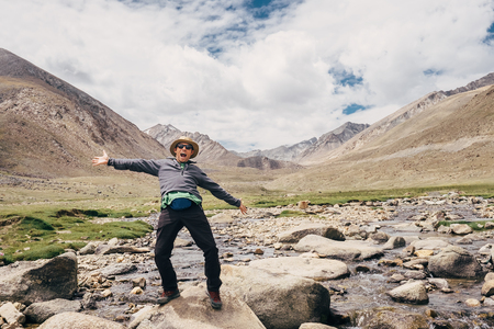 Happy traveler wide opened the arms and cheerful laughing in the indian Himalaya mountains