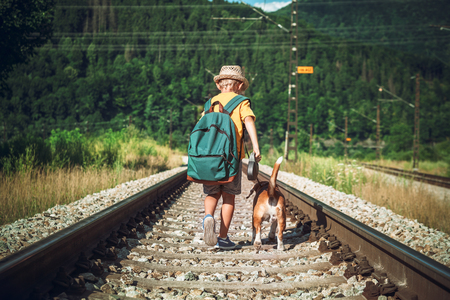 Little boy with backpack walks with beagle dog on the emty railway in forest