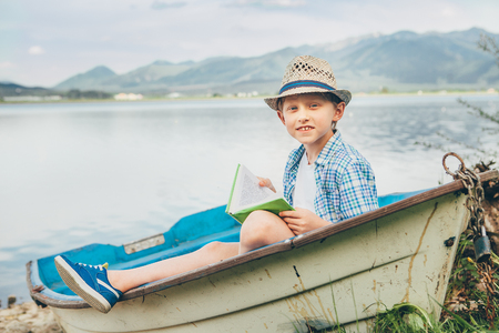 Boy reads a book sitting in old boat on the lake bank