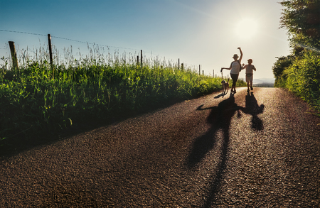 Mother, son and dog walk on country sunset road and make funny cartoon shadows Stock Photo