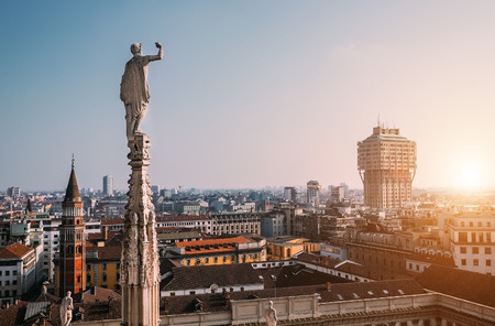 One of numerous statues of main Cathedral in Milan looks on modern city Imagens