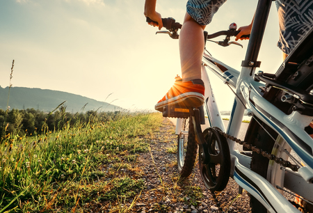 Boy feet in red sneackers on bicycle pedal close up image Stock Photo