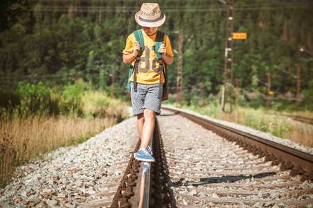 Little boy with backpack walks on railway track Foto de archivo