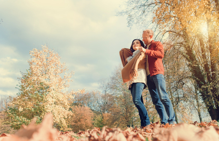 tender tenderness: Man covers his wife shoulders with warm shawl in autumn park Stock Photo