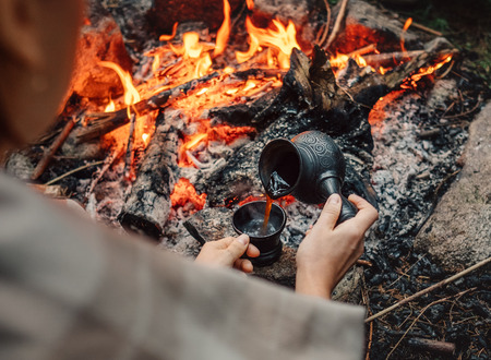Woman makes a coffee on campfire Stock Photo