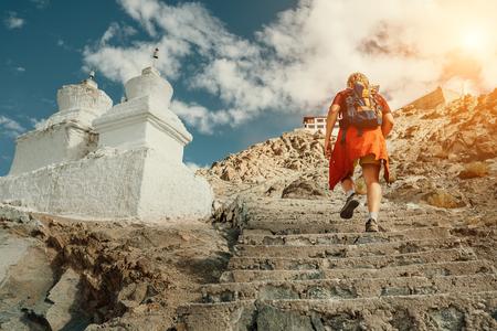 Toeristische man beklapt trappen naar tibetan heilige plaats in de Himalaya berg Stockfoto