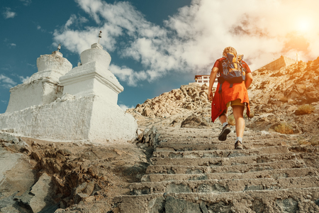 Tourist man climbs up stairs to tibetan holy place in Himalaya mountain