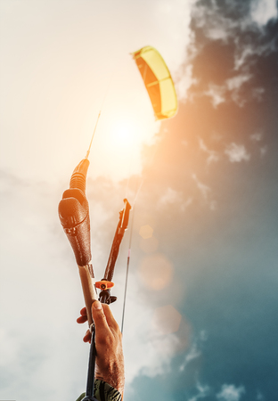 kiteboarding: Close up image kitesurfers hand with kite in blue sky