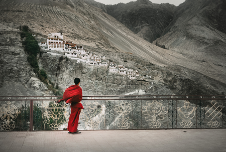 Buddhist Monk in red robe looks on Diskit Monastery, Indian Himalaya