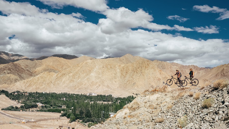 Two bicyclist travelers stay on mountain top