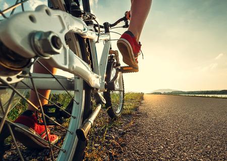 子赤のスニーカーで足が自転車に乗るを開始します。