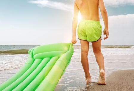 Boy mit grünen Schwimmen Matratze steht auf seasurf Linie Standard-Bild - 83086989