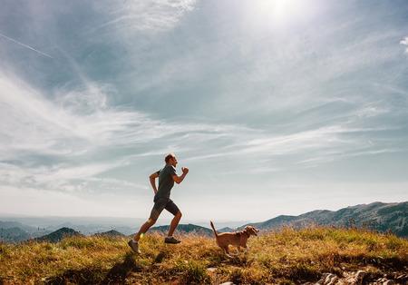 山の頂上で彼のビーグル犬と一緒に走っている人 写真素材