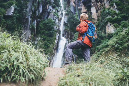 Tourist man with backback rest near the waterfall in rainy forest Stock fotó