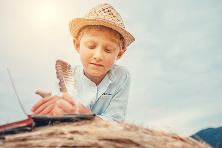 Boy reads a book lying on hay roll
