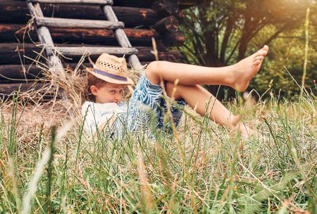 Little boy rest in green grass near the hayloft in garden