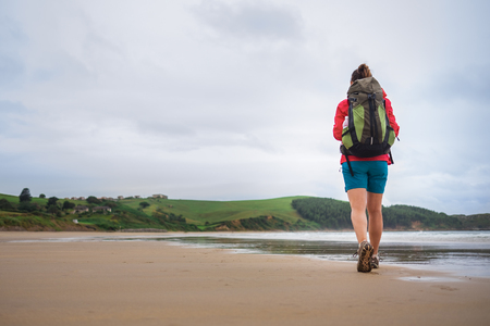 Backpacker girl traveler walk on deserted ocean beach. Asturias, Spain.
