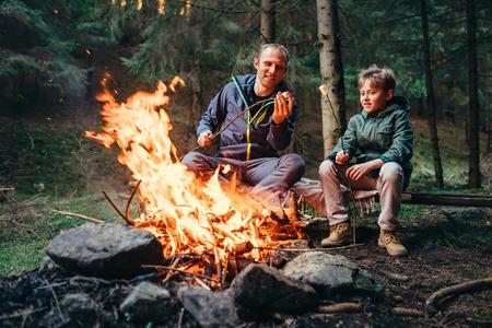 Father and son roast marshmallow on campfire Фото со стока
