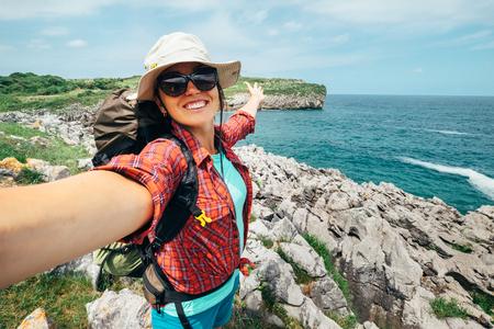 Feliz mujer mochilero viajero tomar una foto selfie en la costa increíble del océano. Asturias. España Foto de archivo - 83349525