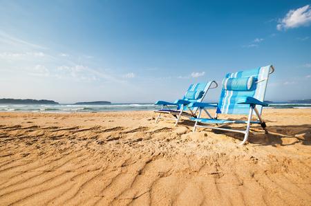 2 つの青い長いすが砂海ビーチです。