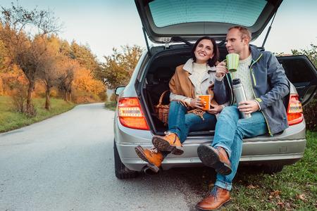 자동차 트렁크에 차 파티 - 사랑의 부부는 차 트렁크에 앉아 보온병 플라스크에서 뜨거운 차를 마신다. 스톡 콘텐츠